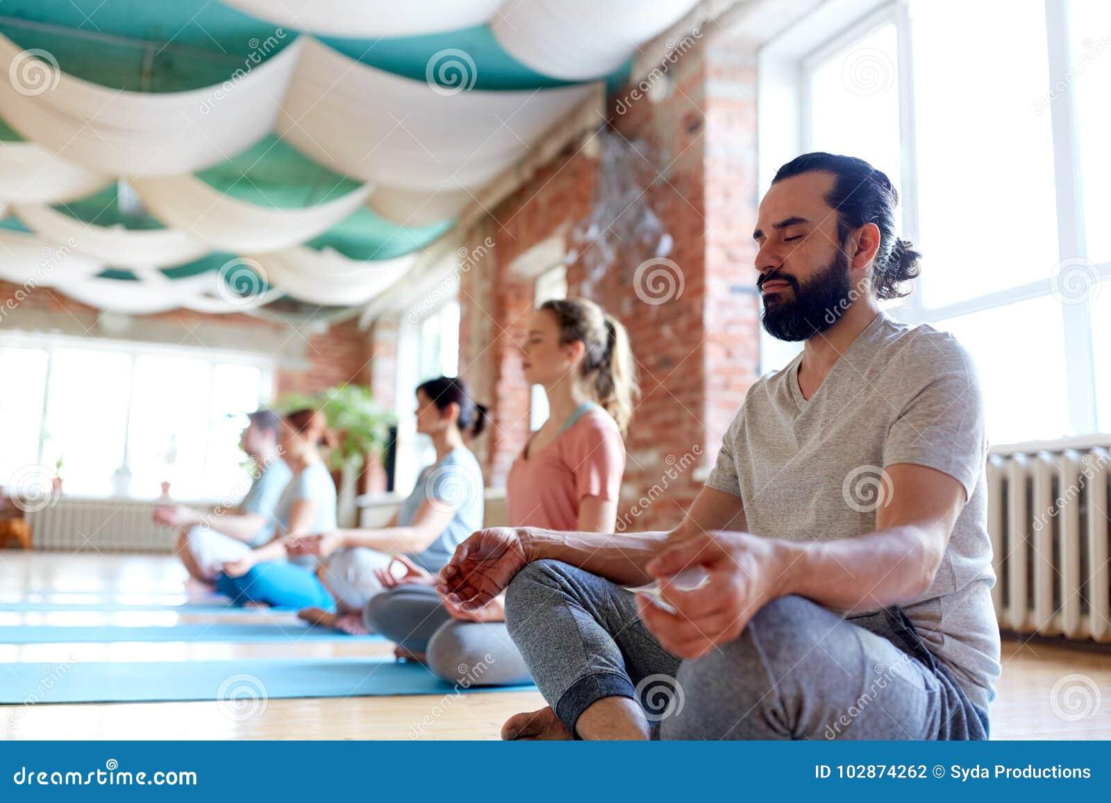 Uomo con il gruppo di persone che meditano allo studio di yoga