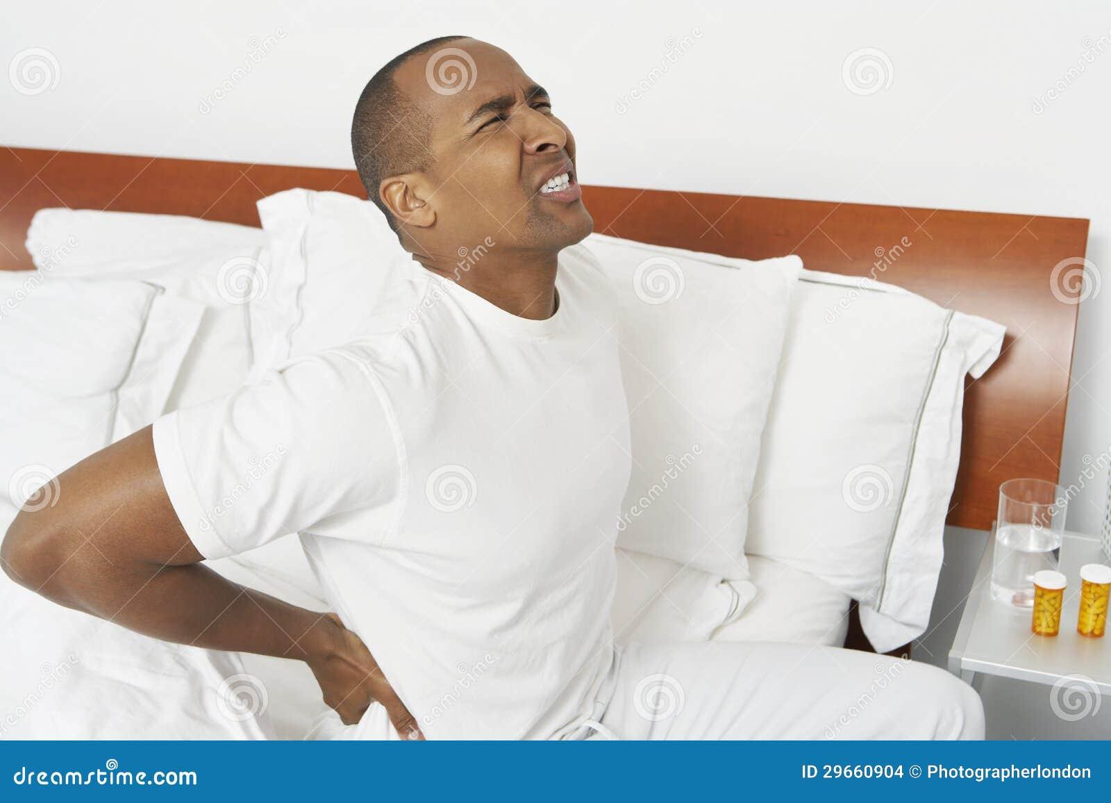 Uomo con il mal di schiena a letto immagini stock - Mal di schiena a letto cause ...