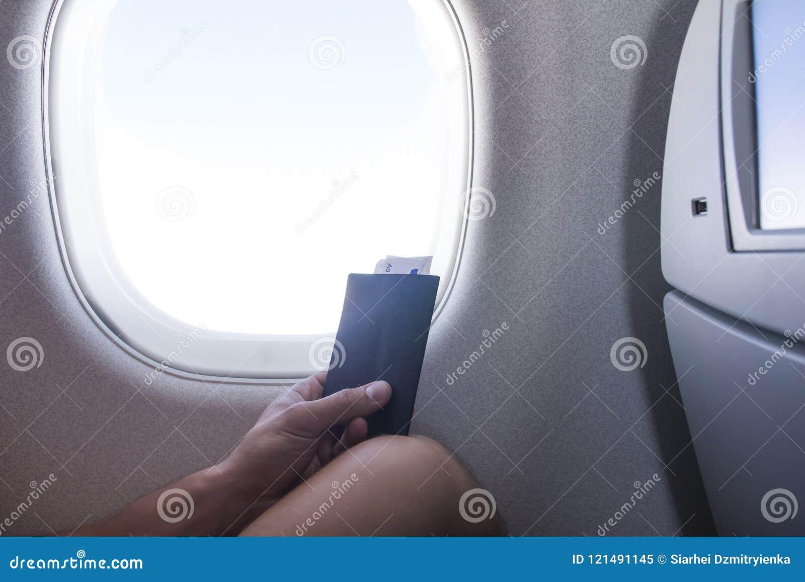 Uomo con il passaporto e biglietto che si siede accanto alla finestra nel viaggio di vacanza dell aeroplano della cabina di aerei