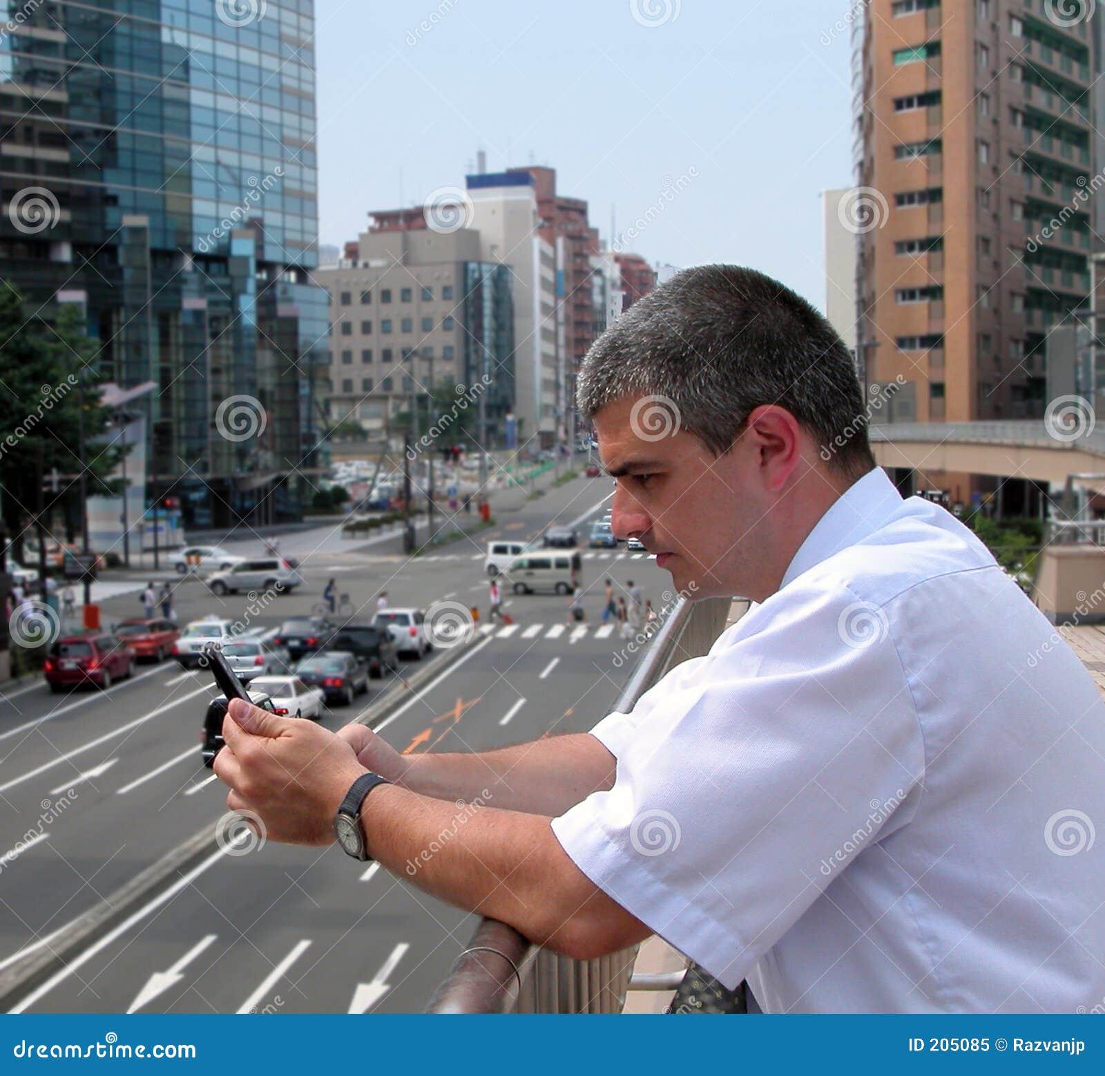 Uomo con il telefono mobile in una città