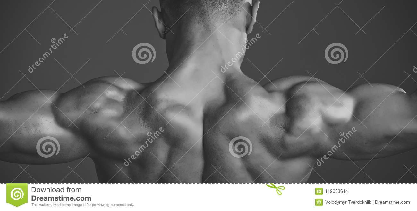 Uomo con l ente e la parte posteriore bagnati muscolari Sportivo della vettura che mostra il bicipite ed il tricipite