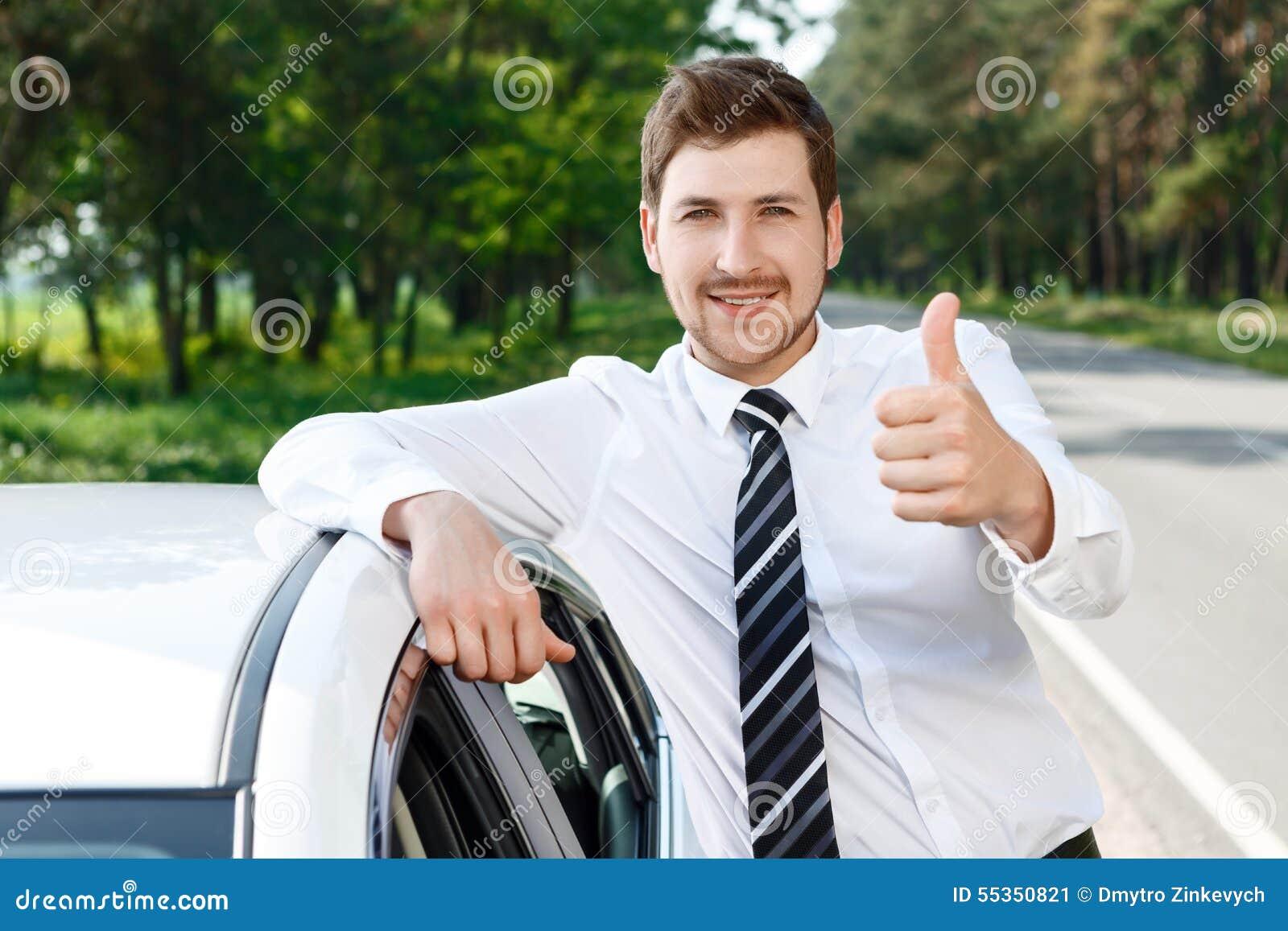 Uomo con la barba che sfoglia sull automobile vicina