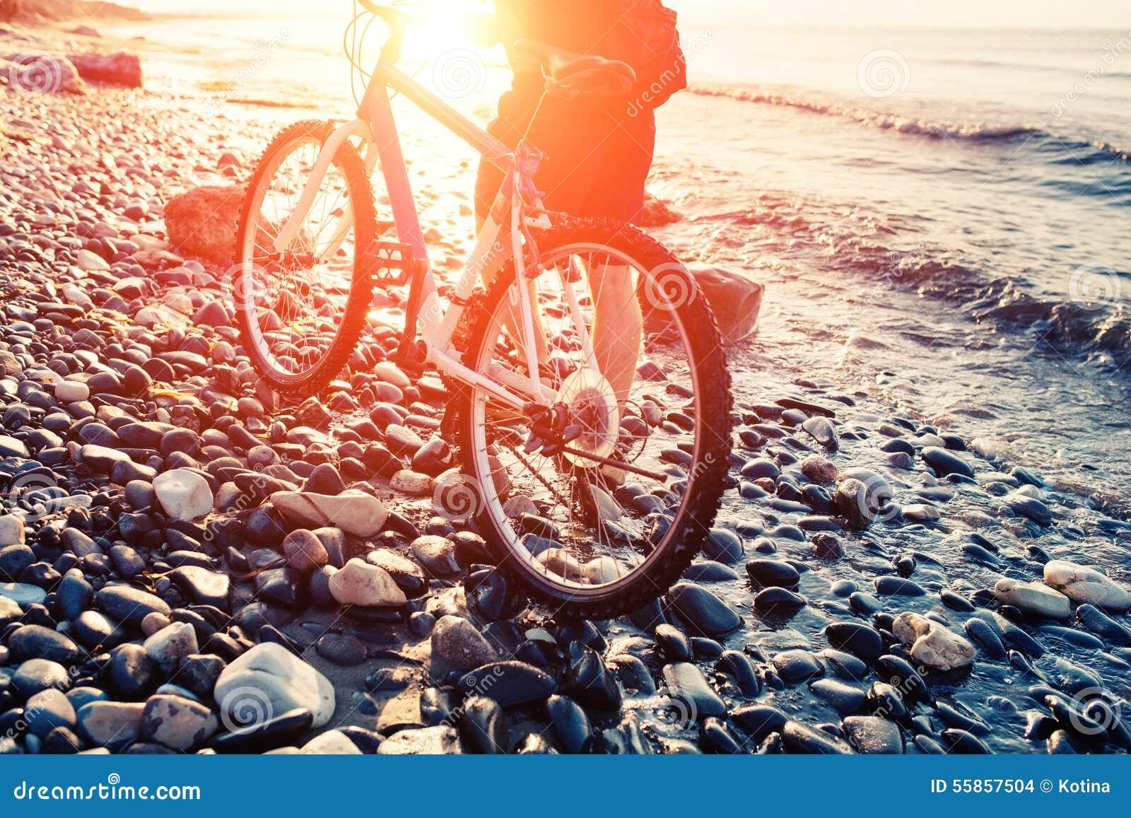 Uomo Con La Bicicletta Su Un Tramonto Della Riva Di Mare Fotografia