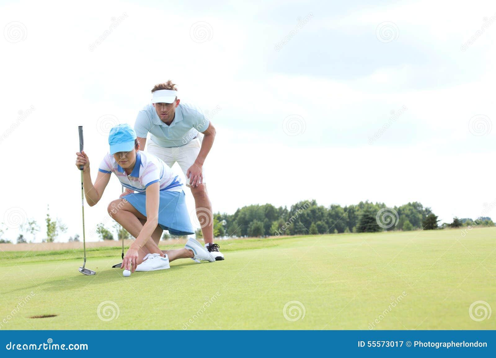 Uomo con la donna che tende palla sul campo da golf contro il cielo
