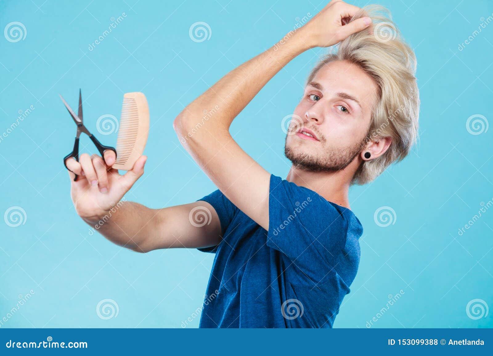 Uomo con le forbici e pettine che creano nuova pettinatura