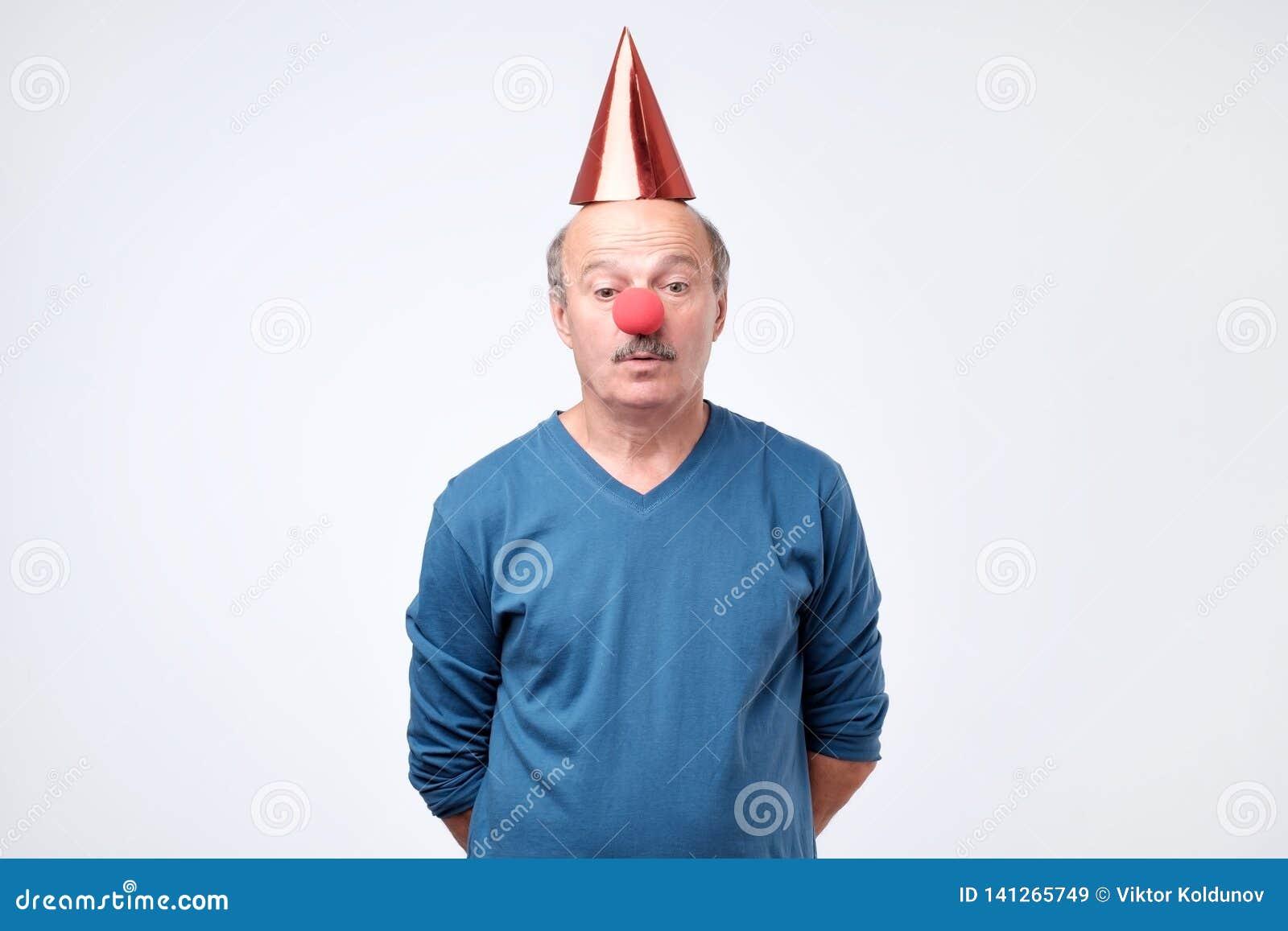 Uomo confuso sugli sguardi del cappello del pagliaccio con l espressione titubante
