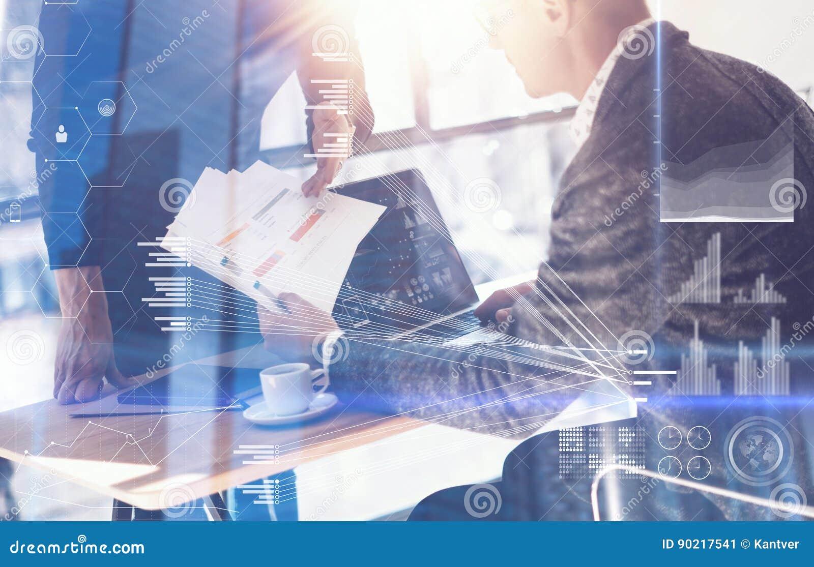 Uomo d affari adulto che lavora computer portatile moderno e che mostra i documenti al giovane collega Concetto dello schermo dig