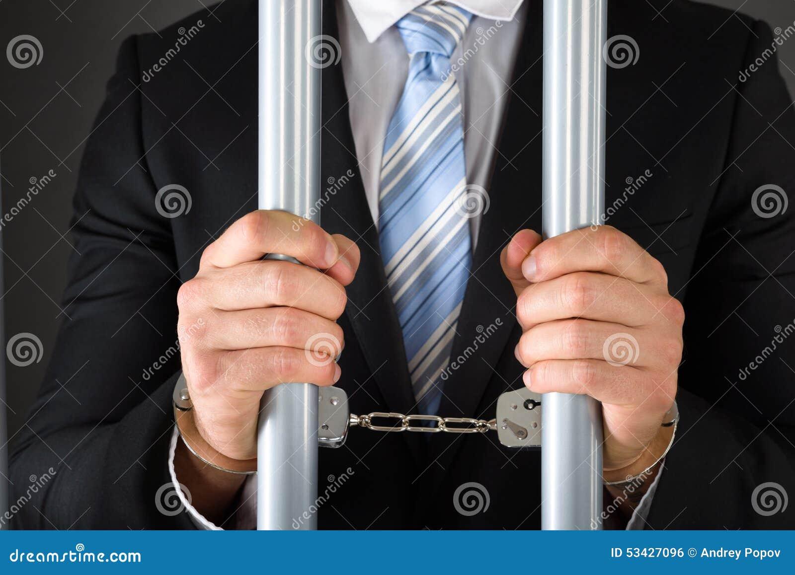 Uomo d affari ammanettato che tiene le barre