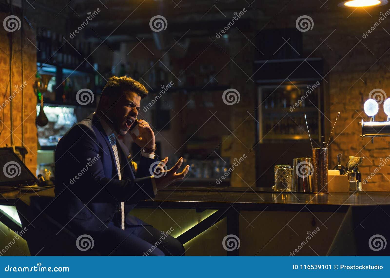 Uomo d affari arrabbiato che rivolge al telefono dalla barra