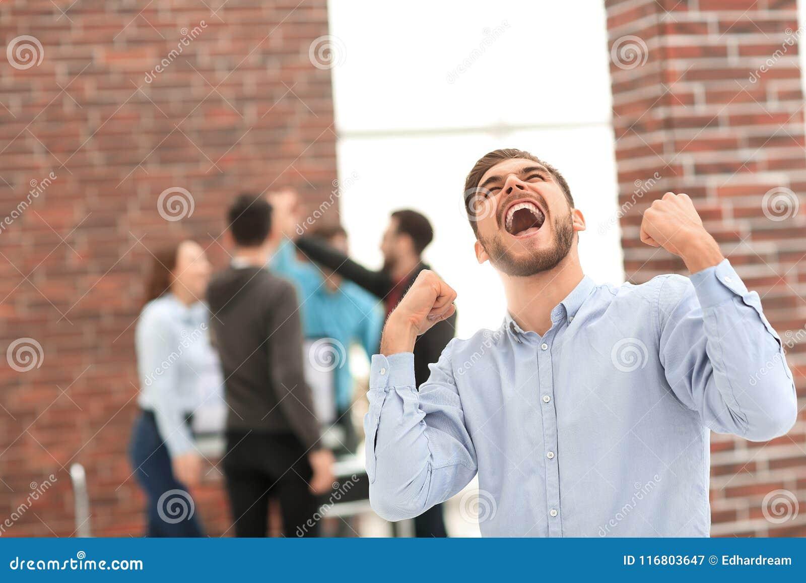 Uomo d affari bello che celebra vittoria che grida felicemente in Th