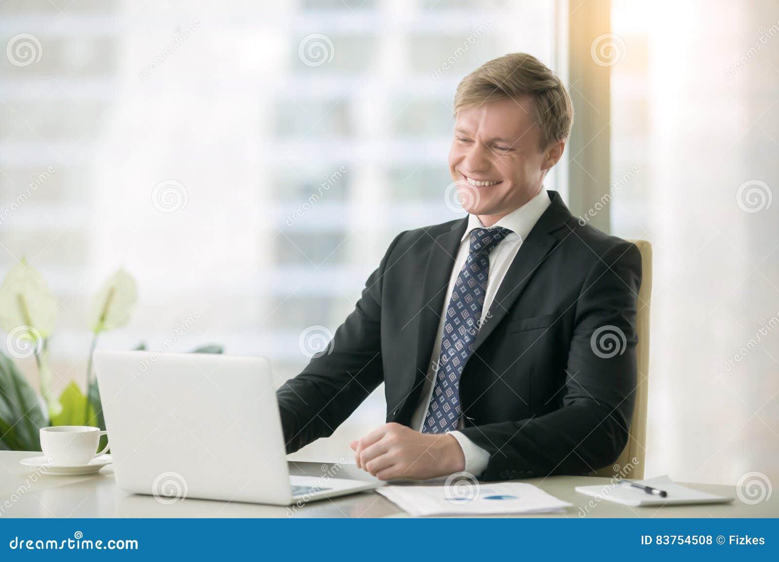 Uomo d affari bello sorridente con il computer portatile