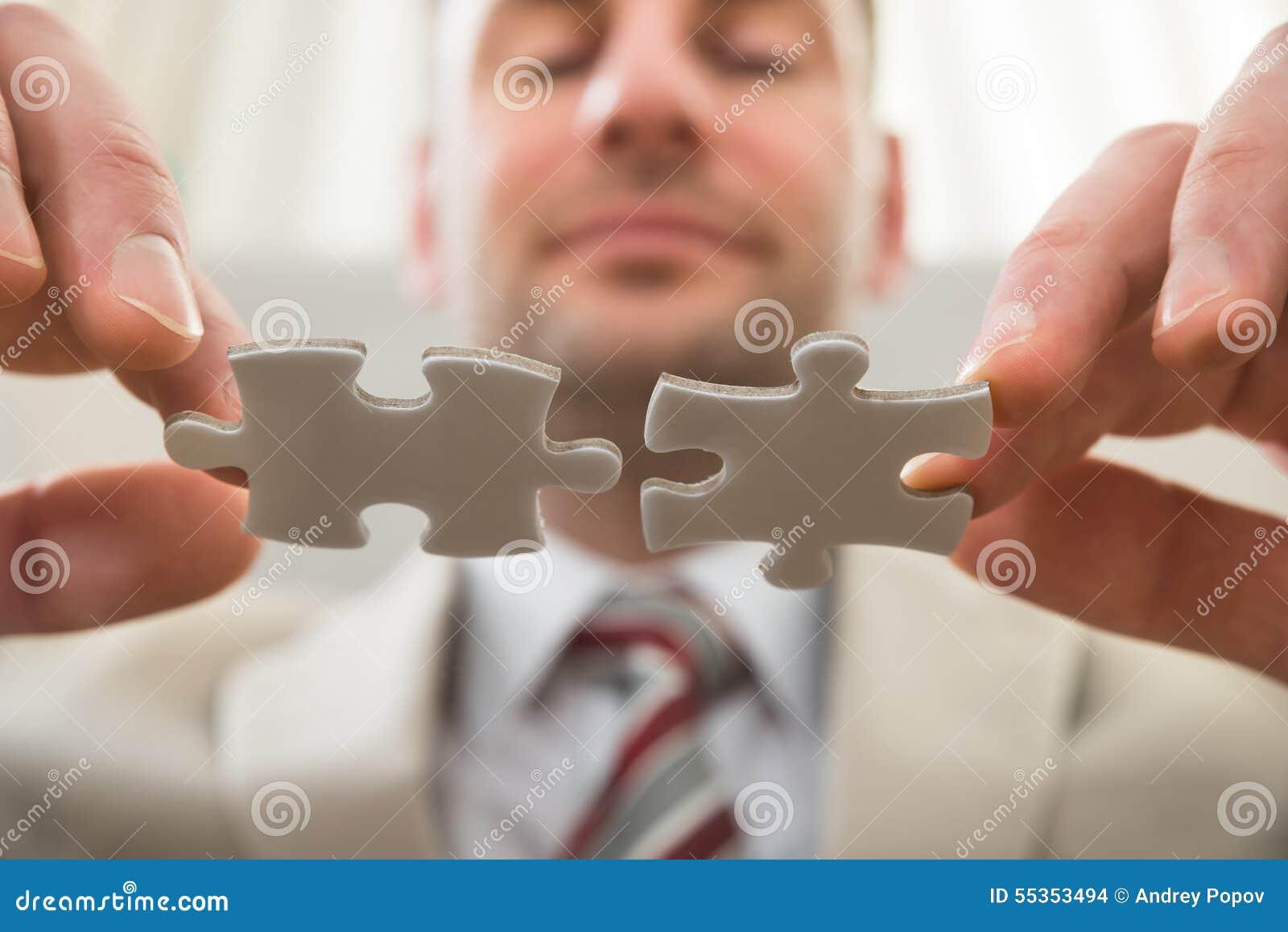 Uomo d affari che collega insieme puzzle