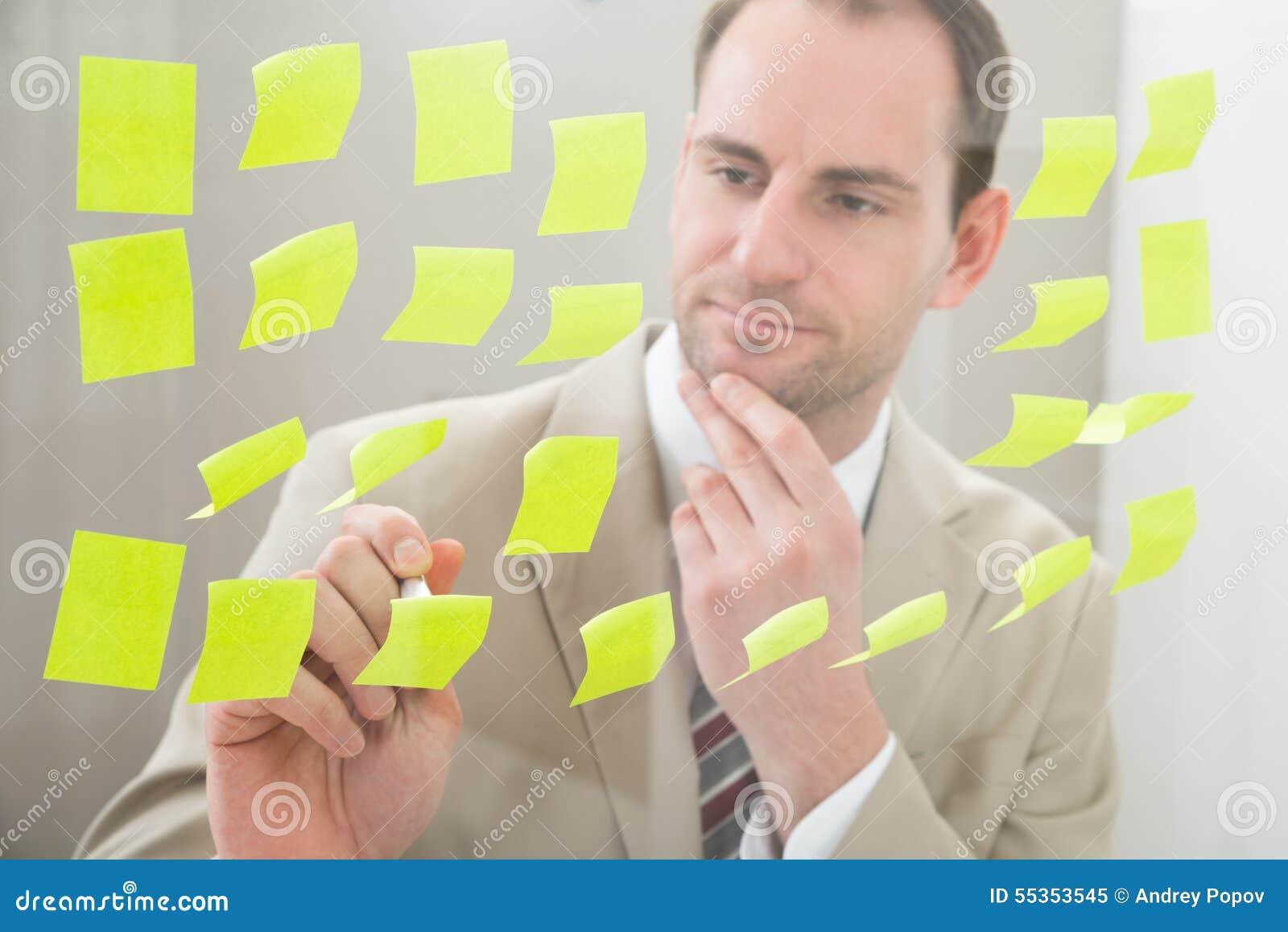 Uomo d affari che fa le note sulla carta adesiva