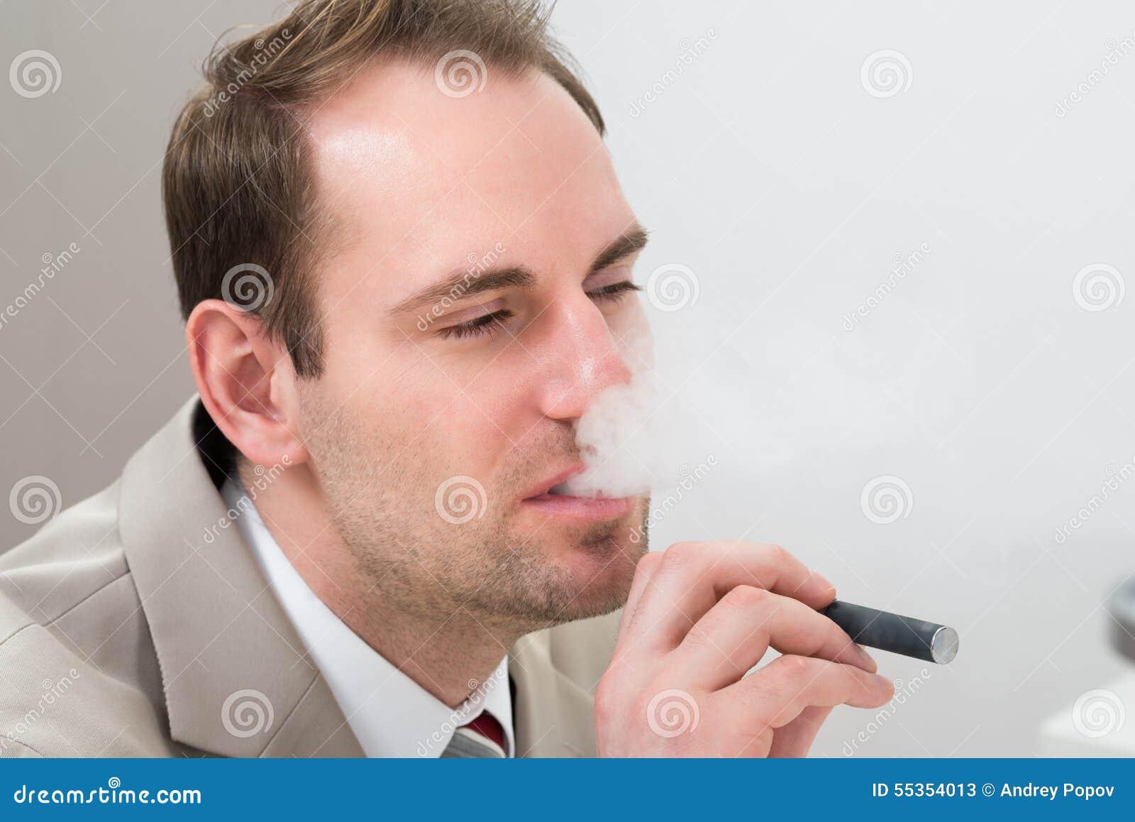 Uomo d affari che fuma sigaretta elettronica