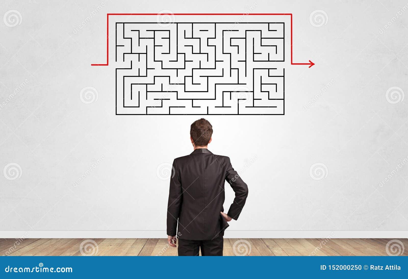 Uomo d affari che guarda ad un labirinto su una parete