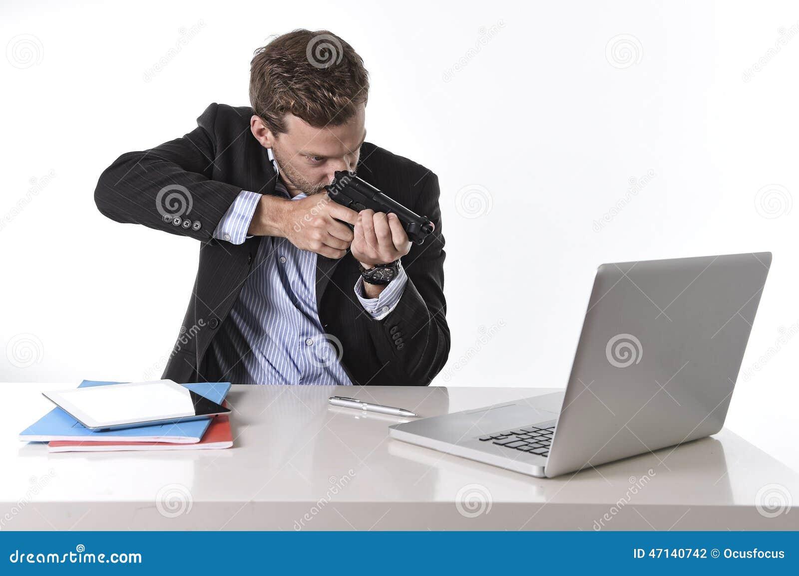 Uomo d affari che indica pistola il computer nel concetto del lavoro straordinario e di lavoro eccessivo