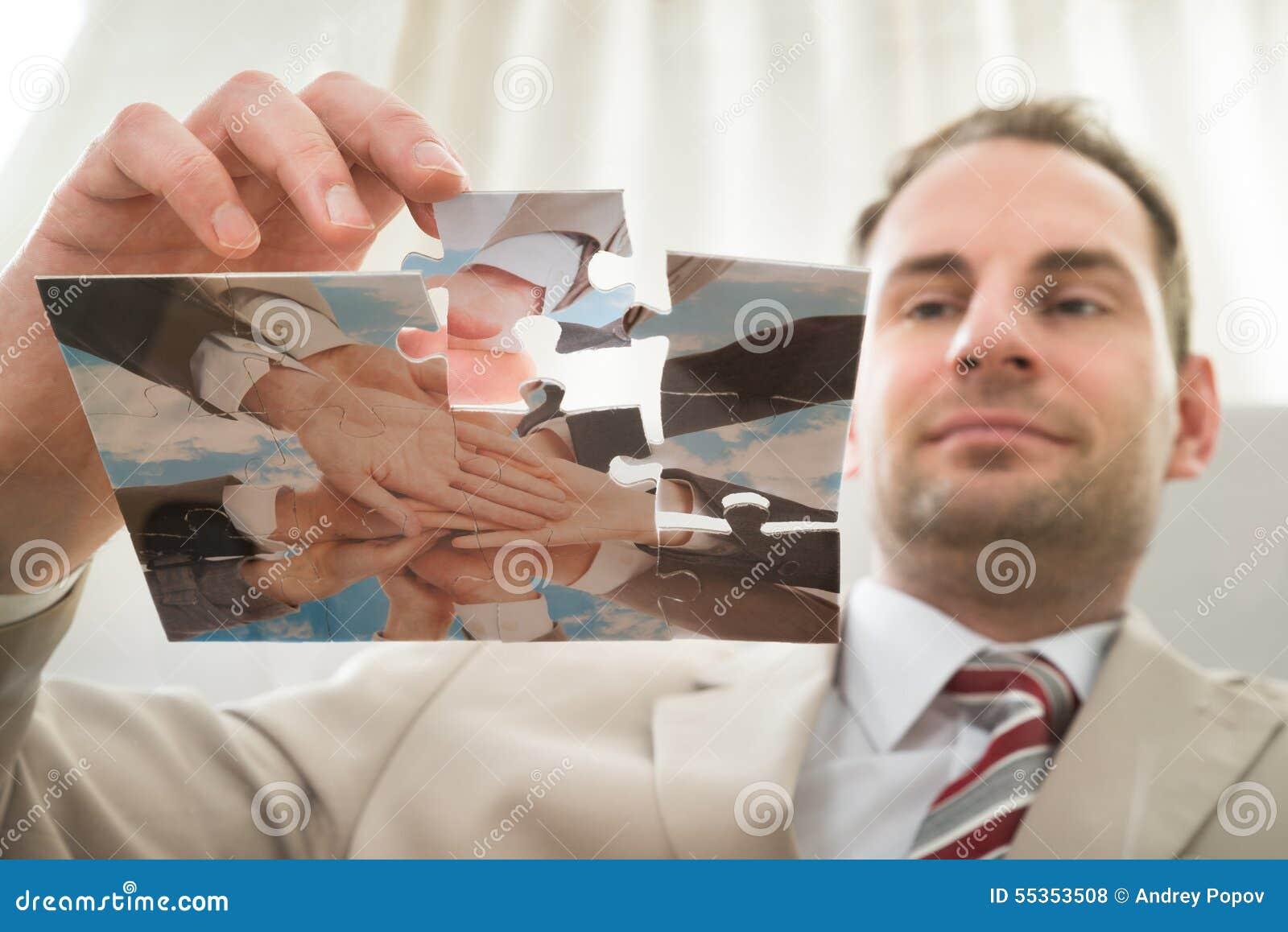 Uomo d affari che inserisce l ultimo pezzo di puzzle