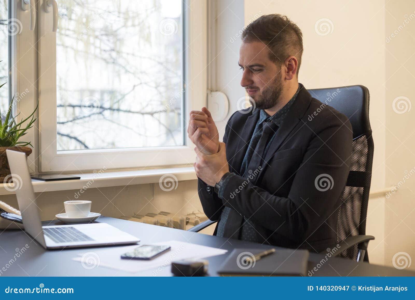 Uomo d affari che lavora al computer portatile nel dolore del polso dell ufficio