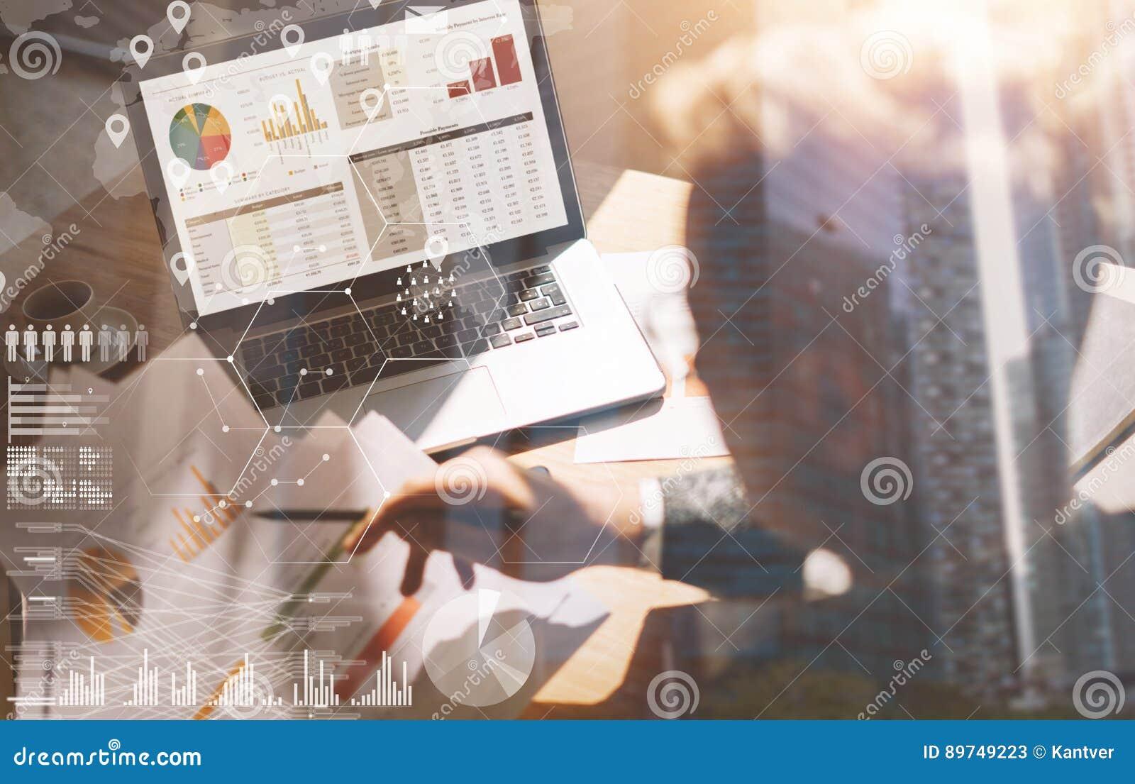 Uomo d affari che lavora all ufficio sul computer portatile Documenti cartacei della tenuta dell uomo in mani Concetto dello sche