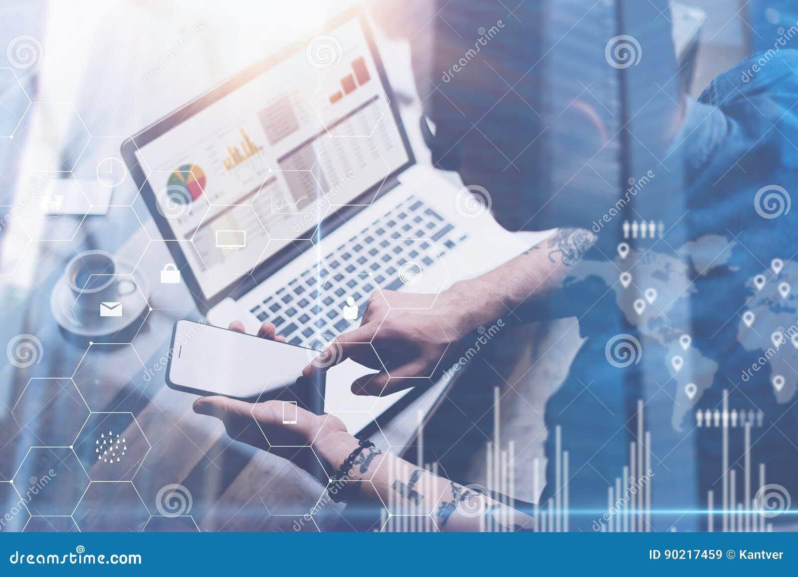 Uomo d affari che lavora all ufficio sul computer portatile Smartphone della tenuta dell uomo in mani Concetto dello schermo digi