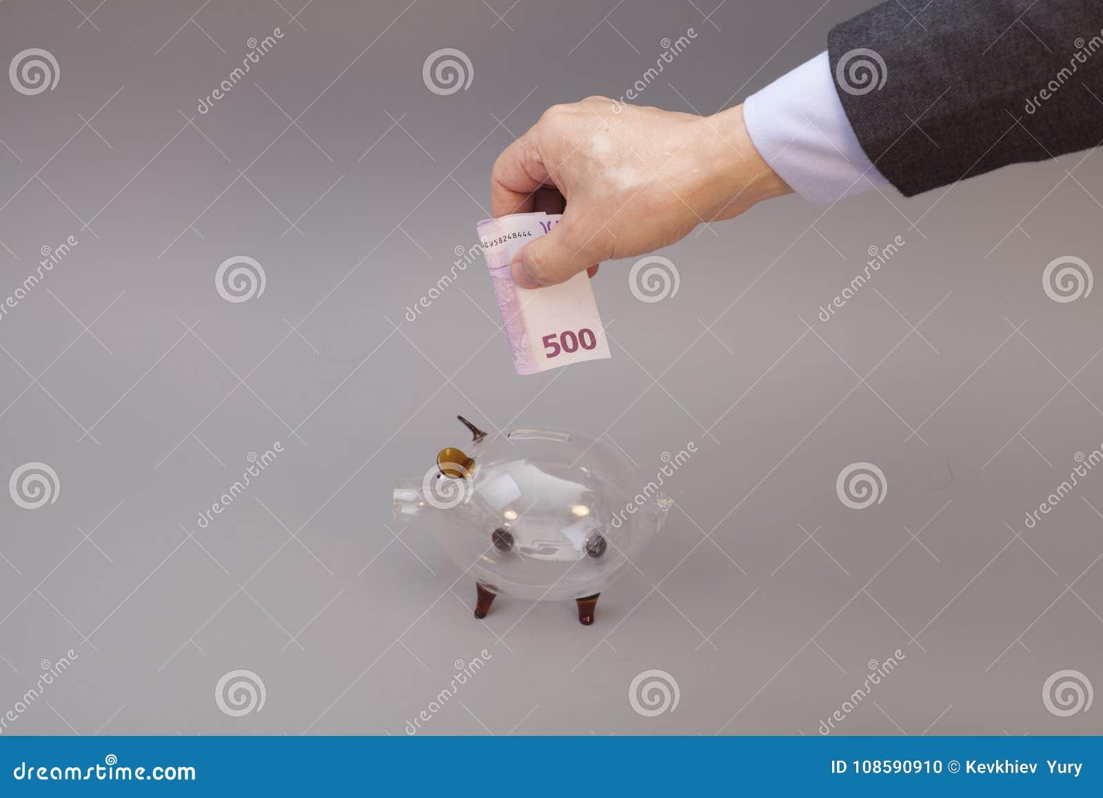 Uomo d affari che mette cinquecento euro nel porcellino salvadanaio di vetro