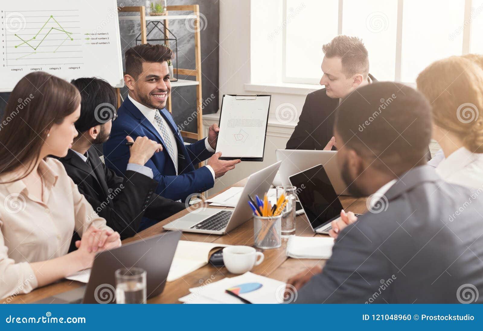 Uomo d affari che mostra rapporto annuale ai suoi colleghi