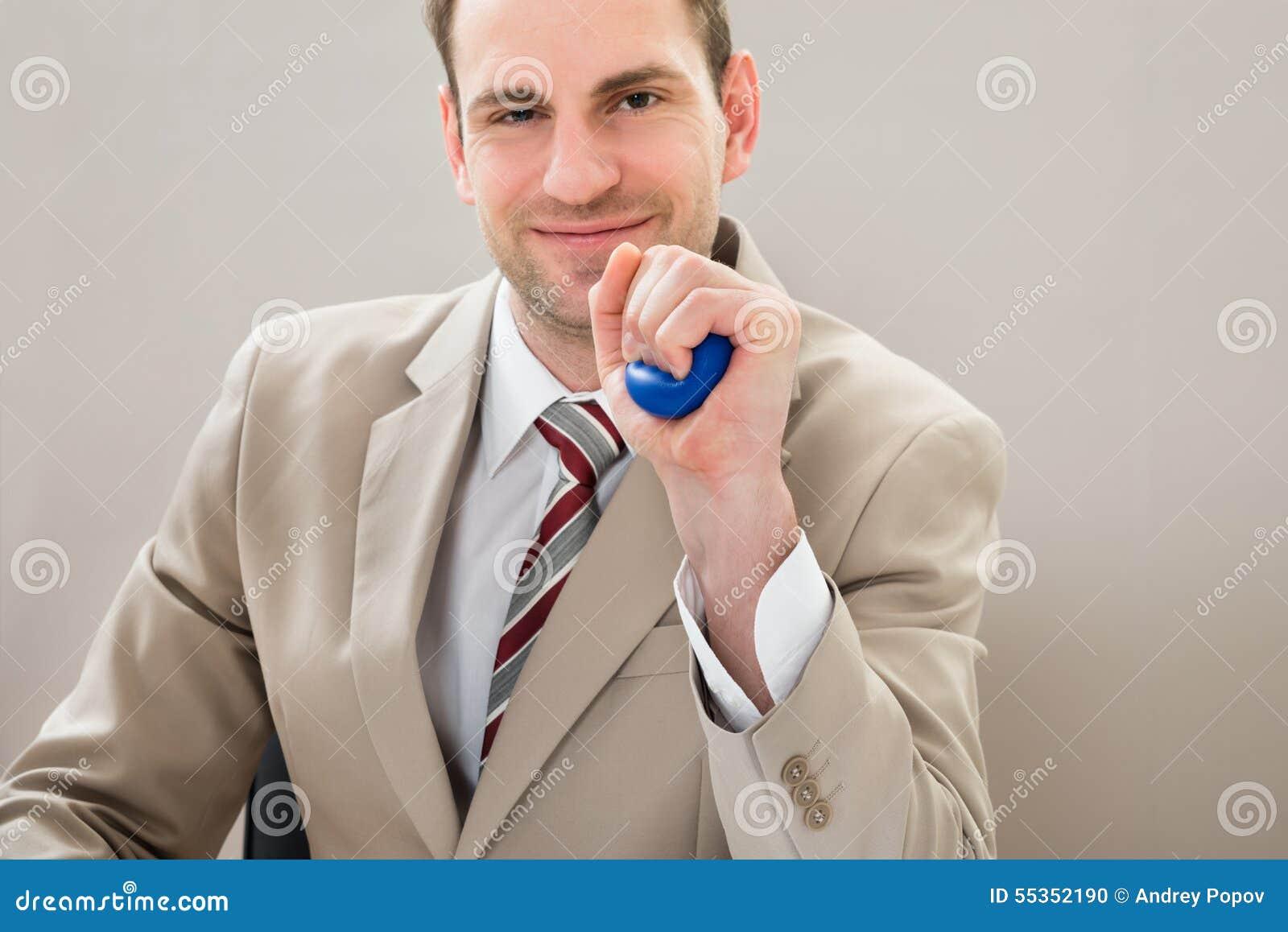 Uomo d affari che schiaccia stressball blu