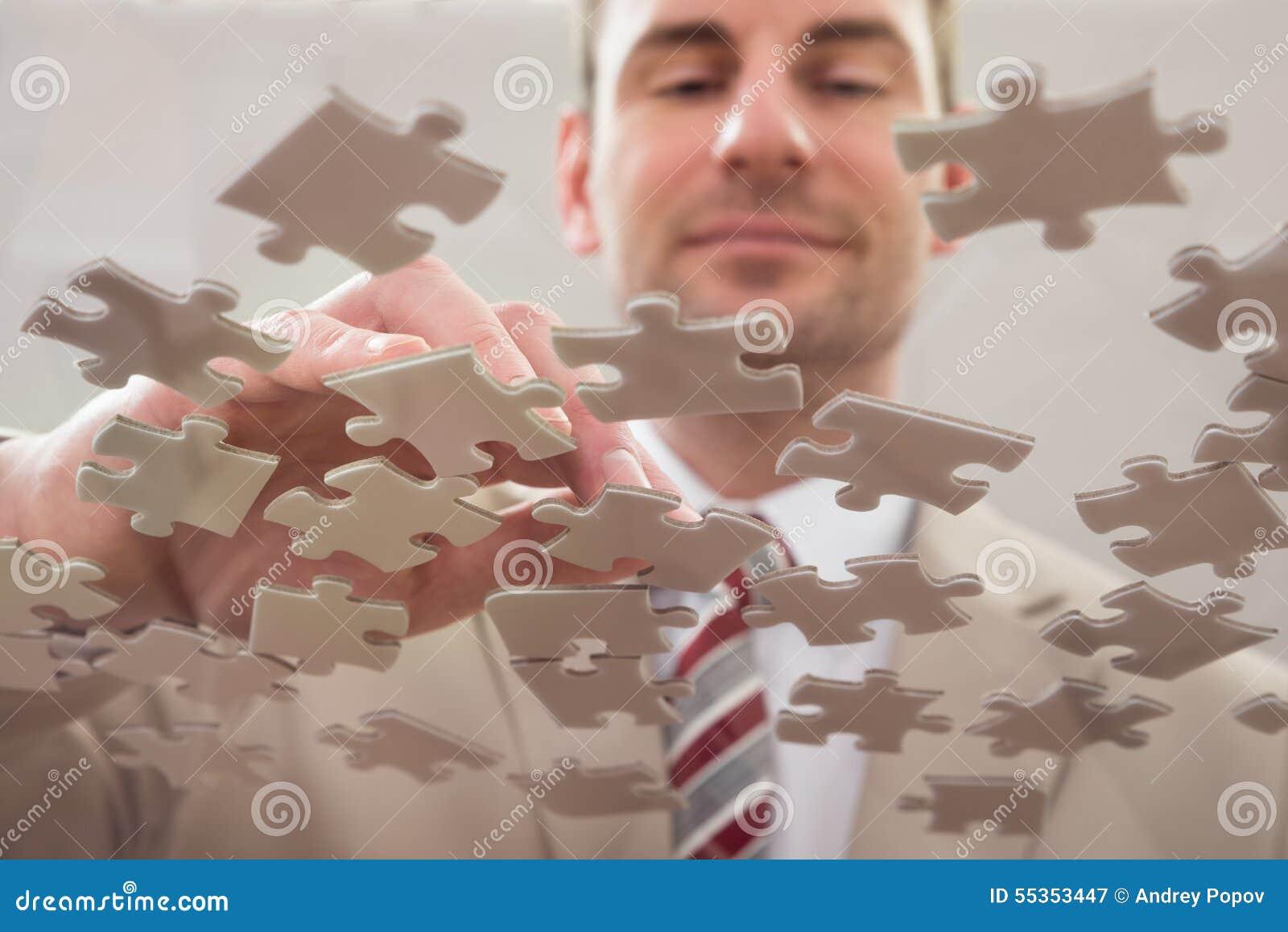 Uomo d affari che separa puzzle