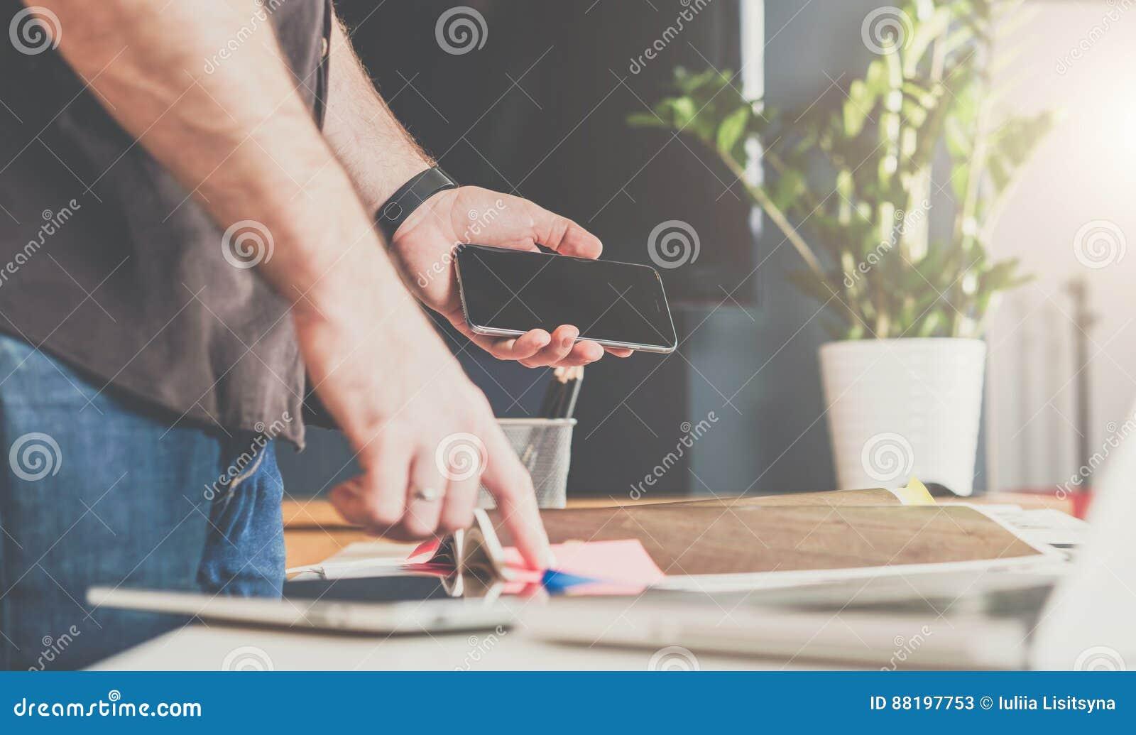 Uomo d affari che sta in un ufficio vicino alla tavola, sfogliante un catalogo e tenente uno smartphone