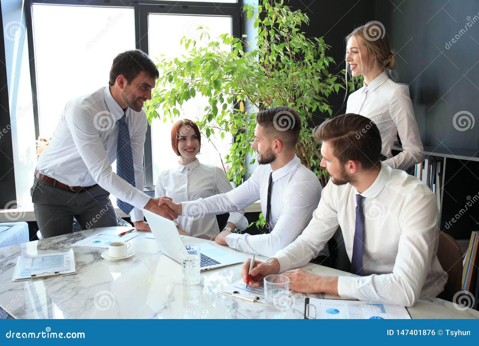 Uomo d affari che stringe le mani per sigillare un affare con il suoi partner e colleghi in ufficio