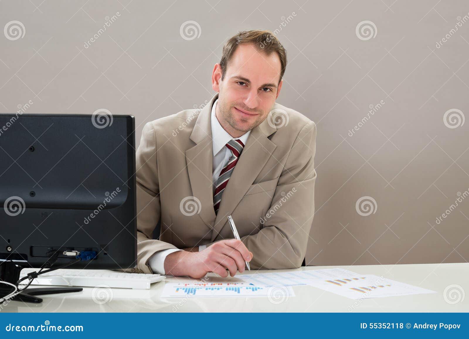 Uomo d affari con i grafici allo scrittorio