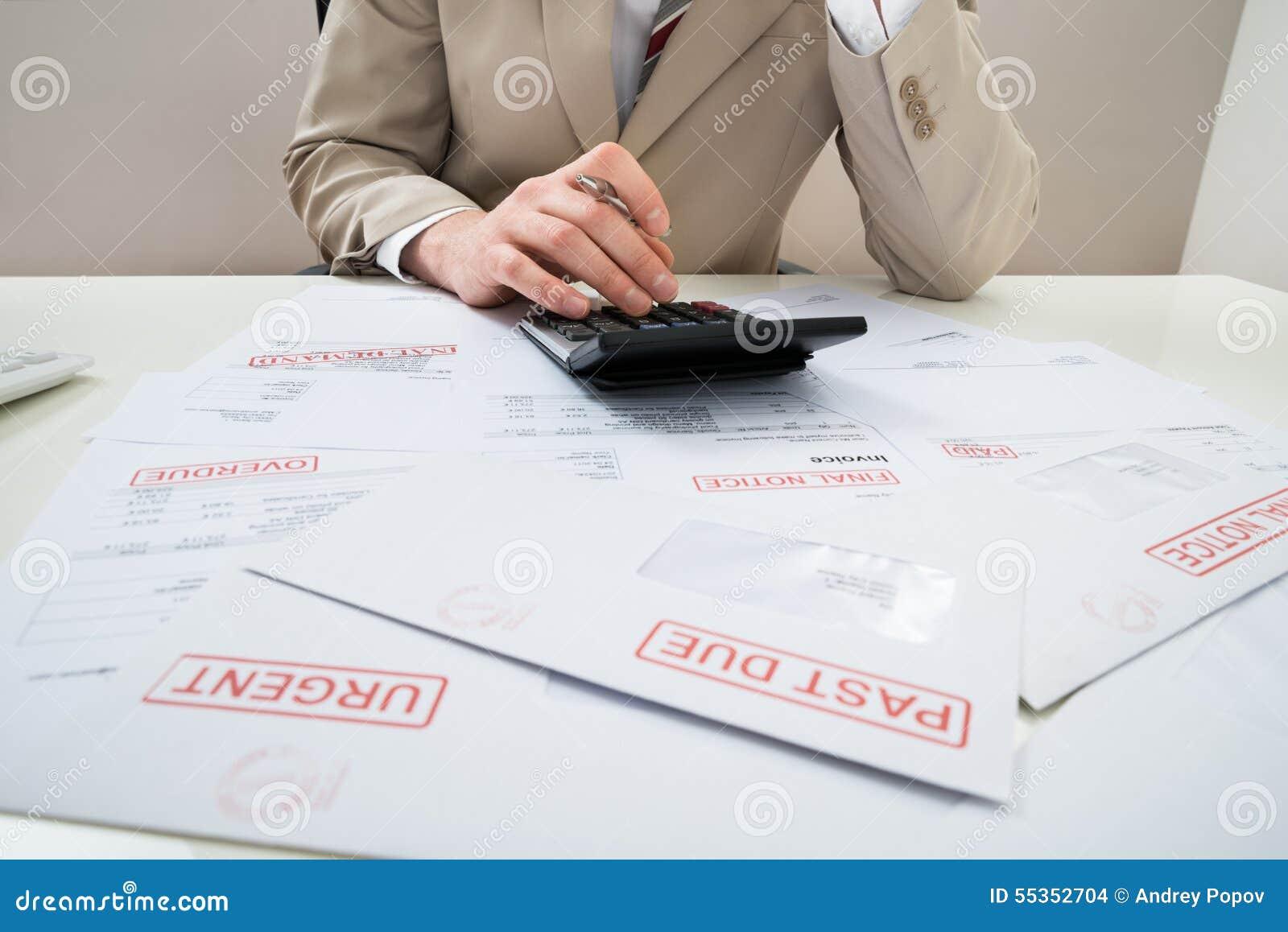 Uomo d affari con il calcolatore e le fatture non pagate