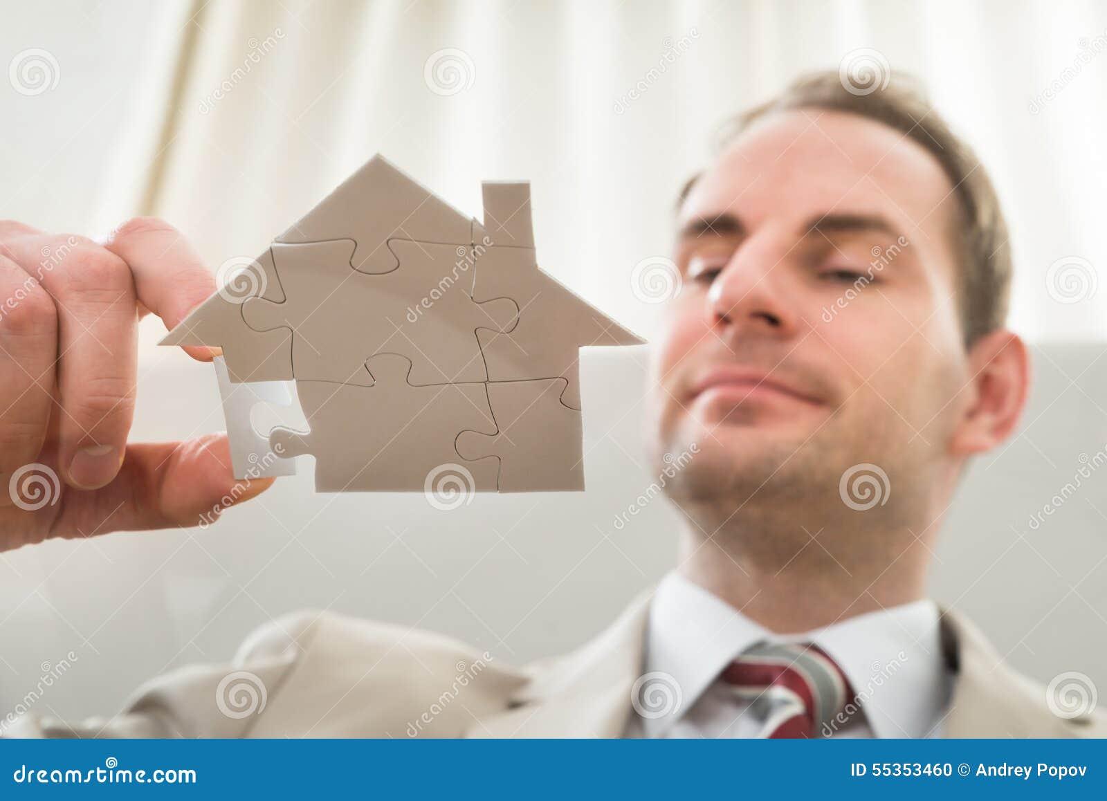 Uomo d affari con il puzzle di forma della casa