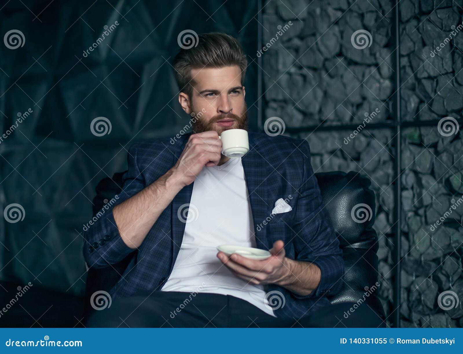 Uomo d affari con la tazza di caffè che colloca contro del fondo moderno