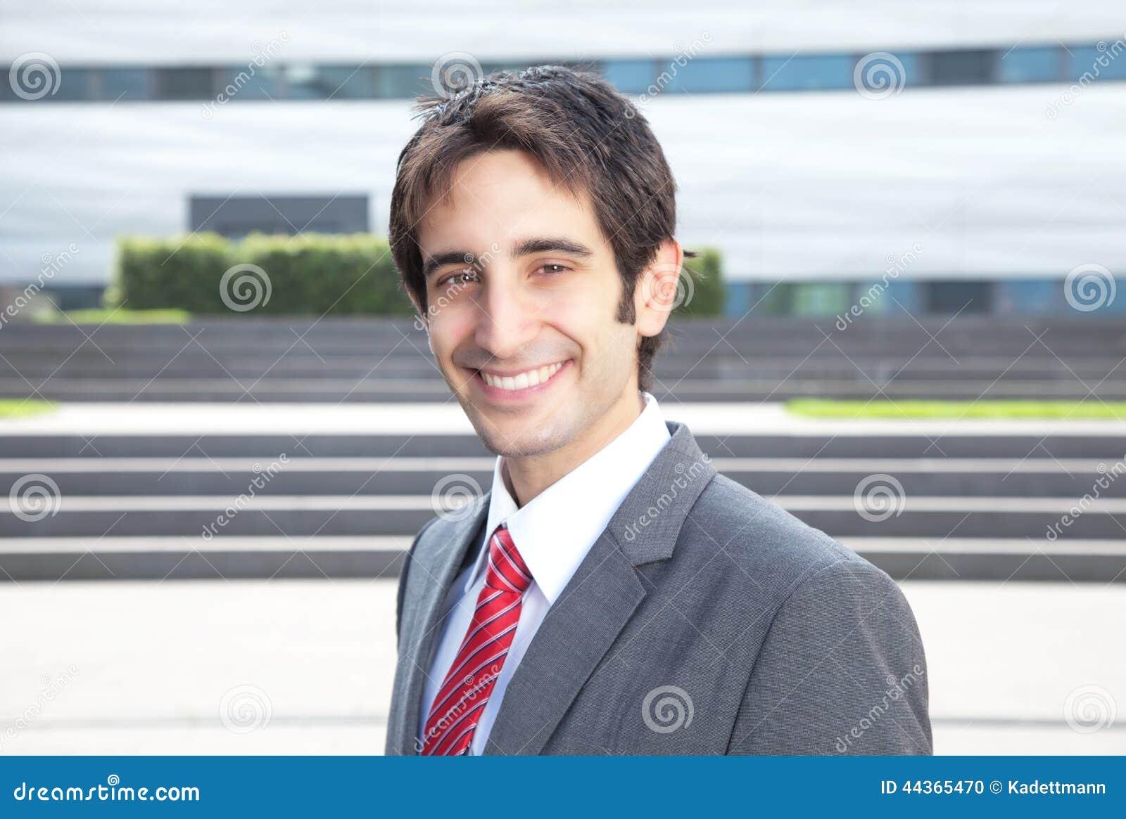 Uomo d affari di risata con capelli neri davanti al suo ufficio