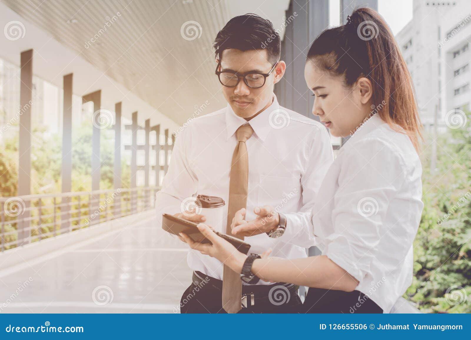 Uomo d affari e donna che per mezzo della compressa di lavoro Riunioni le attività commerciali nella promozione Crei insieme reci
