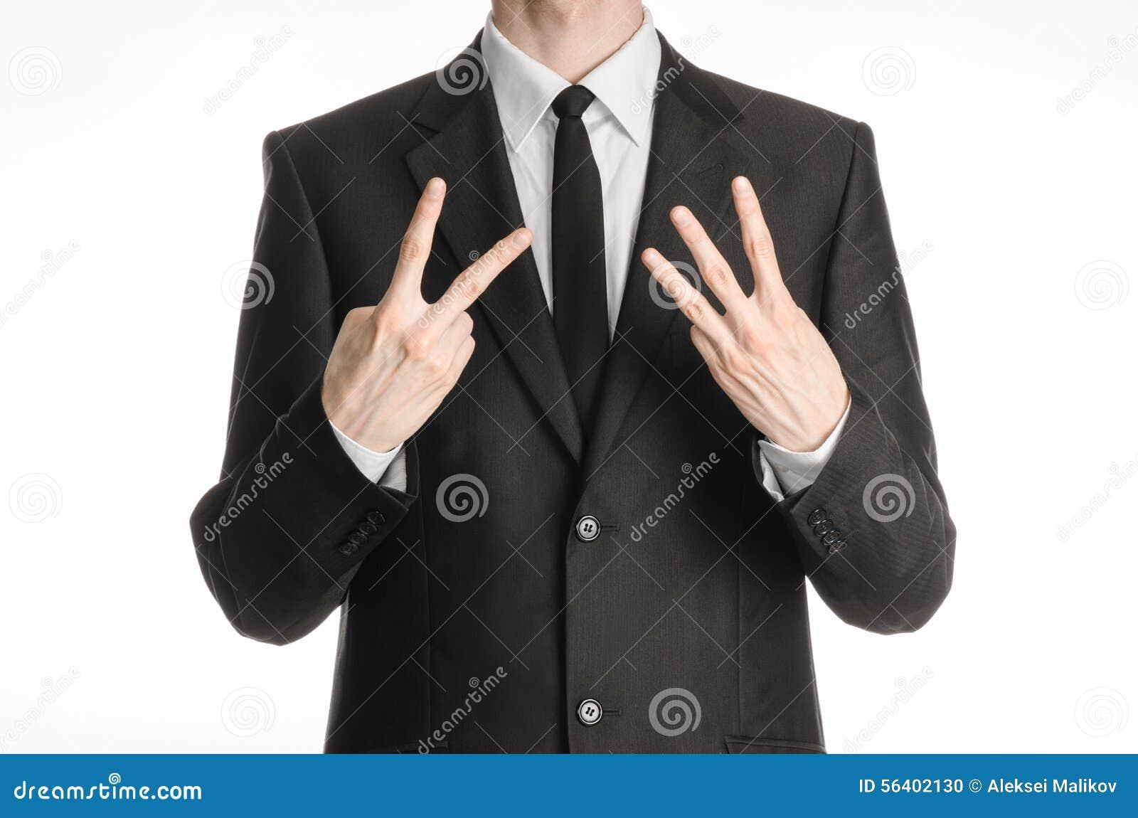 Uomo d affari ed argomento di gesto: un uomo in un vestito nero con un legame che mostra un segno con il suo iso destro del segno
