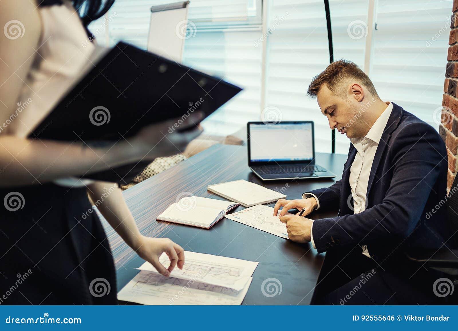 Uomo d affari ed il suo segretario di aiuto nel suo ufficio Il Secre