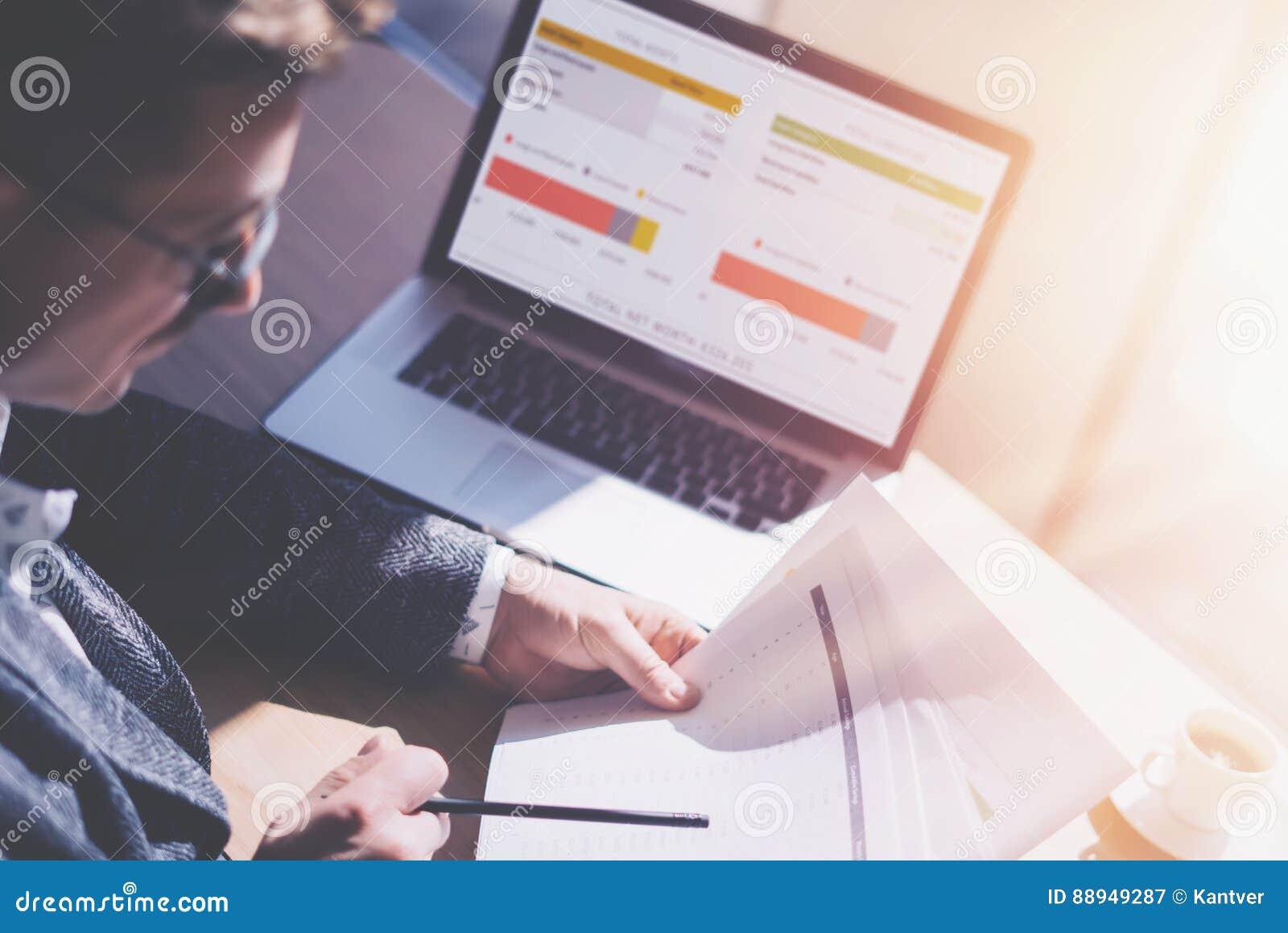 Uomo d affari elegante adulto in occhiali che funzionano all ufficio soleggiato sul computer portatile mentre sedendosi alla tavo