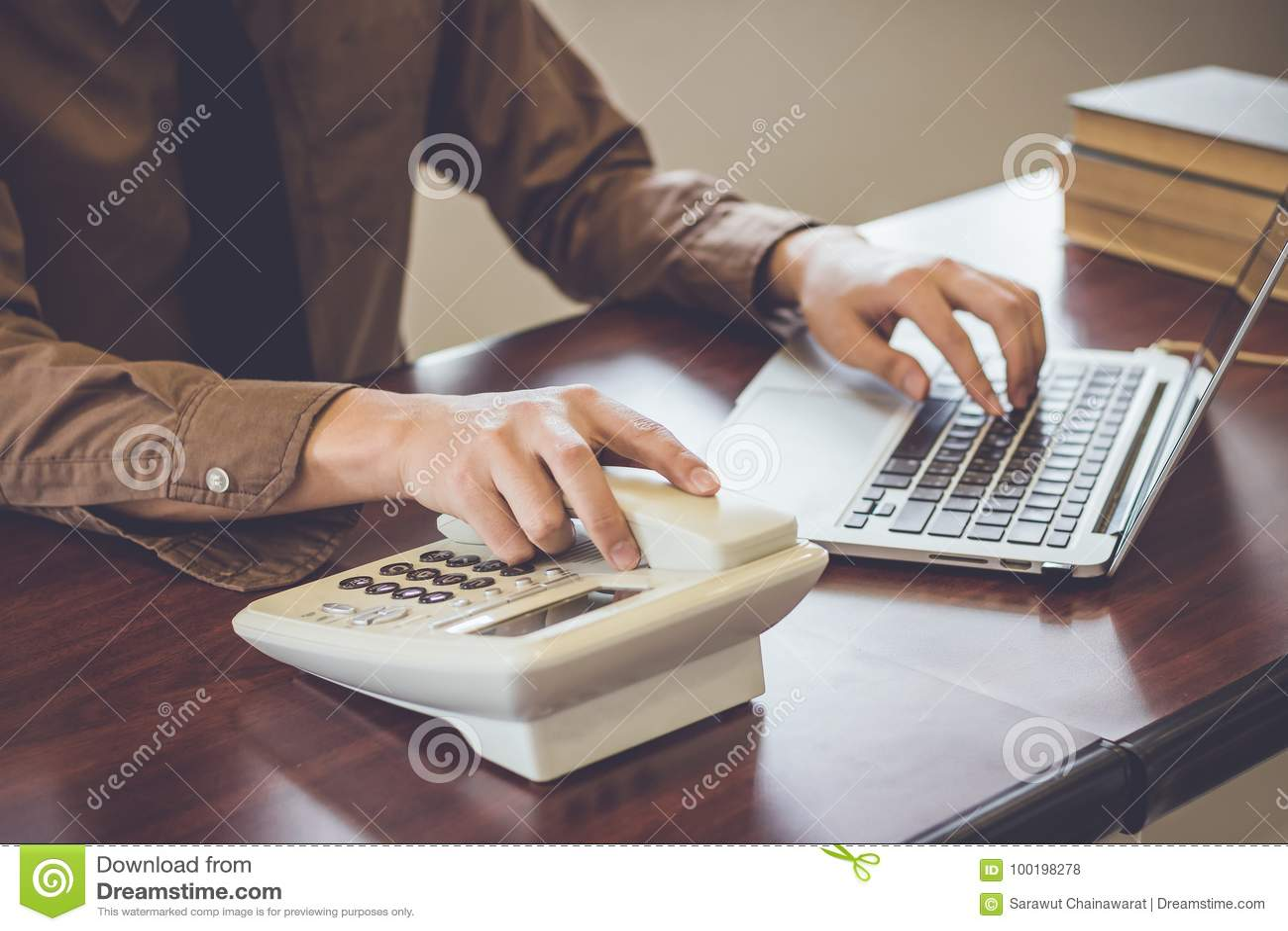 Uomo d affari facendo uso del cliente del contatto telefonico nel tono dell annata dell ufficio