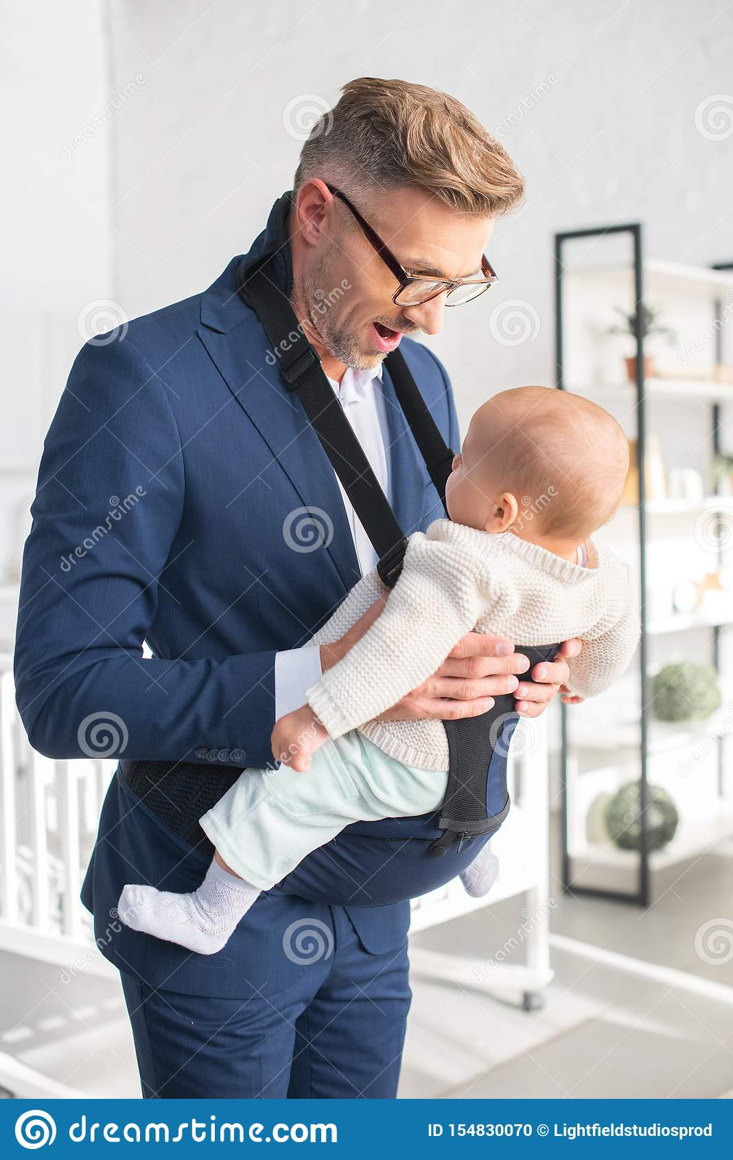 Uomo d affari felice che esamina figlia infantile