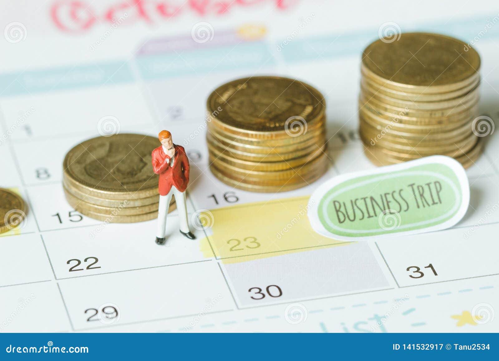 Uomo d affari miniatura sul calendario con le monete della pila usando come impegno del fondo