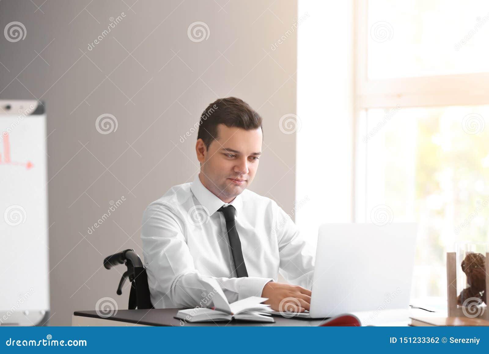 Uomo d affari nel funzionamento della sedia a rotelle con il computer portatile in ufficio