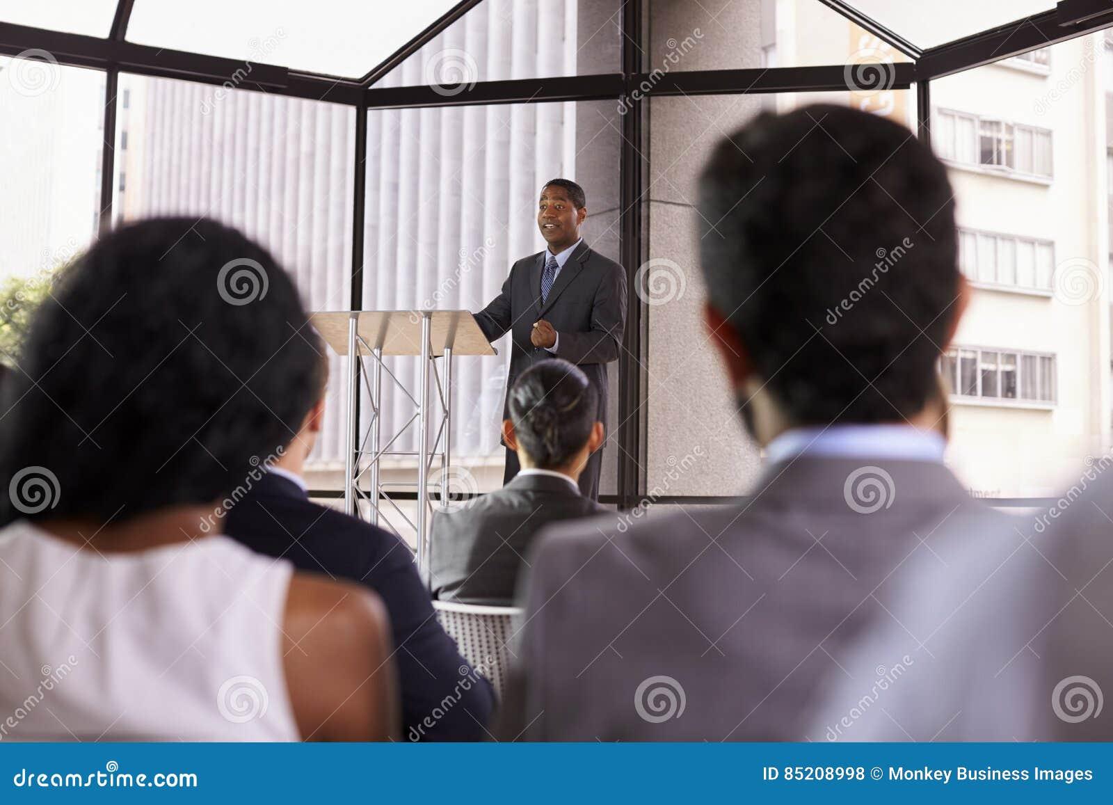 Uomo d affari nero che presenta seminario di affari ad un pubblico
