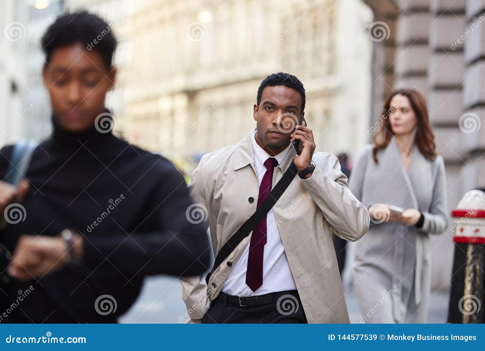 Uomo d affari nero millenario che cammina in una via occupata di Londra facendo uso dello smartphone, fuoco selettivo