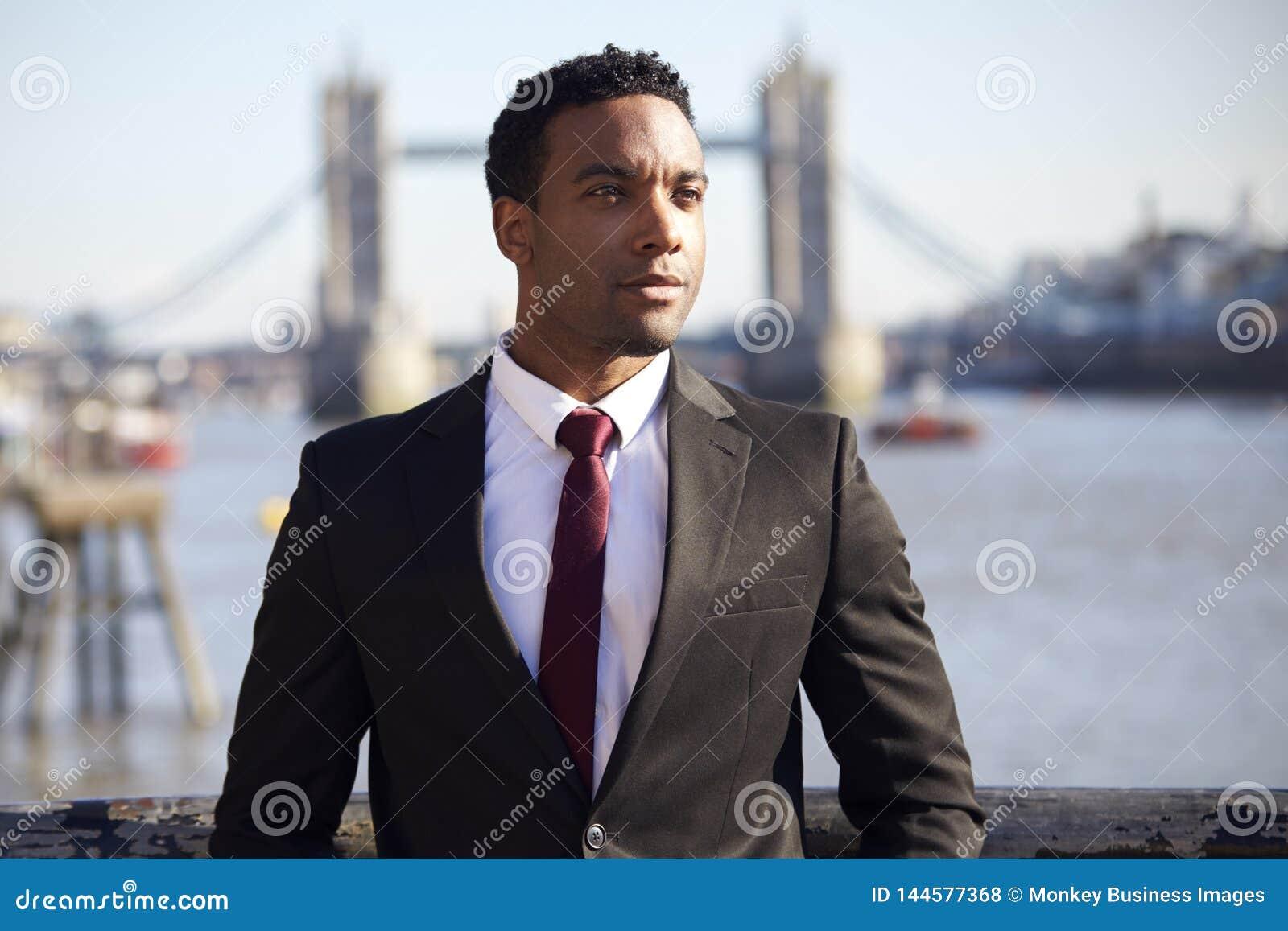 Uomo d affari nero millenario che indossa rivestimento nero, camicia bianca e condizione del legame alla riva del fiume di Tamigi