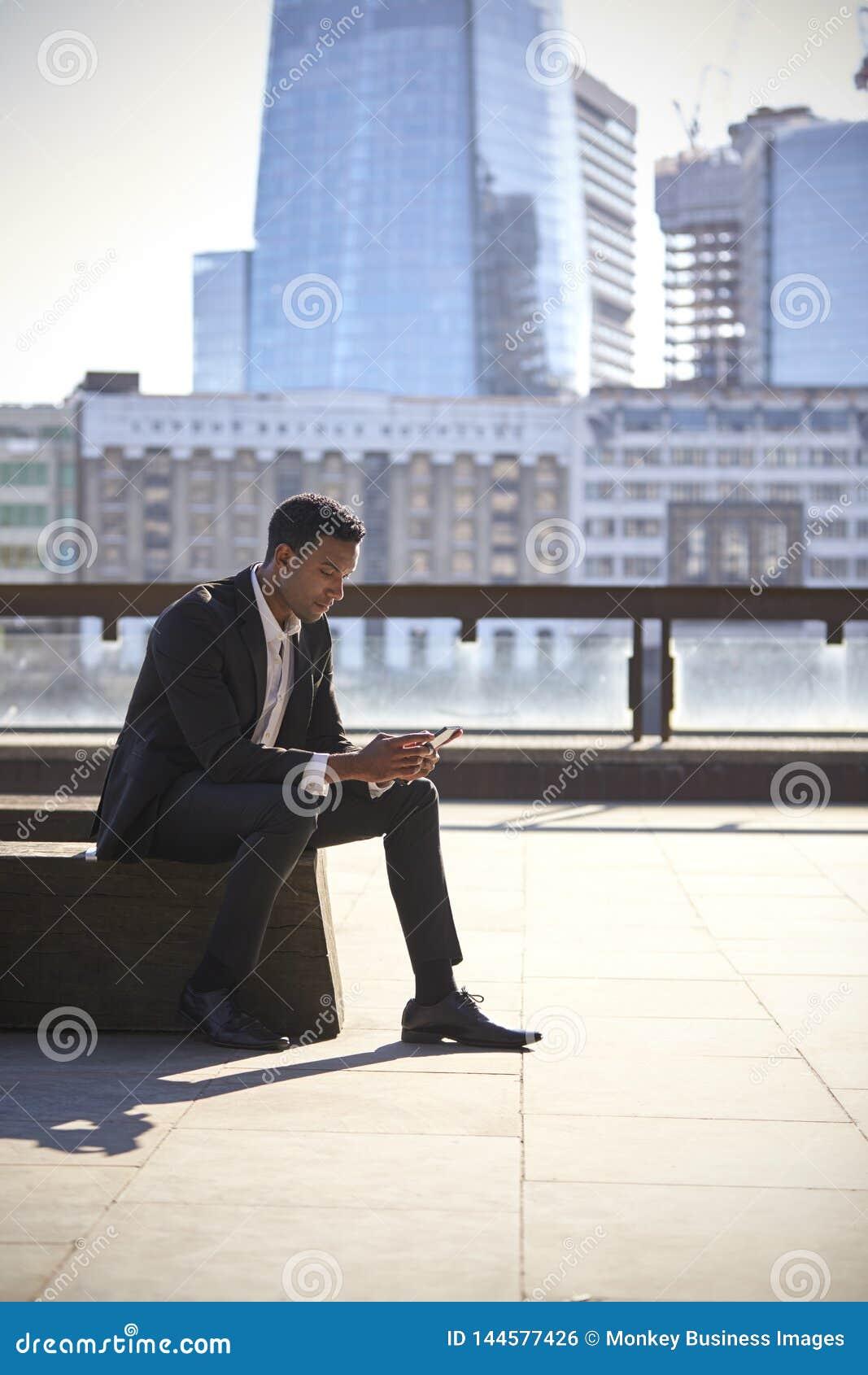 Uomo d affari nero millenario che porta vestito nero e camicia bianca che si siedono sull argine di Tamigi, Londra, facendo uso d