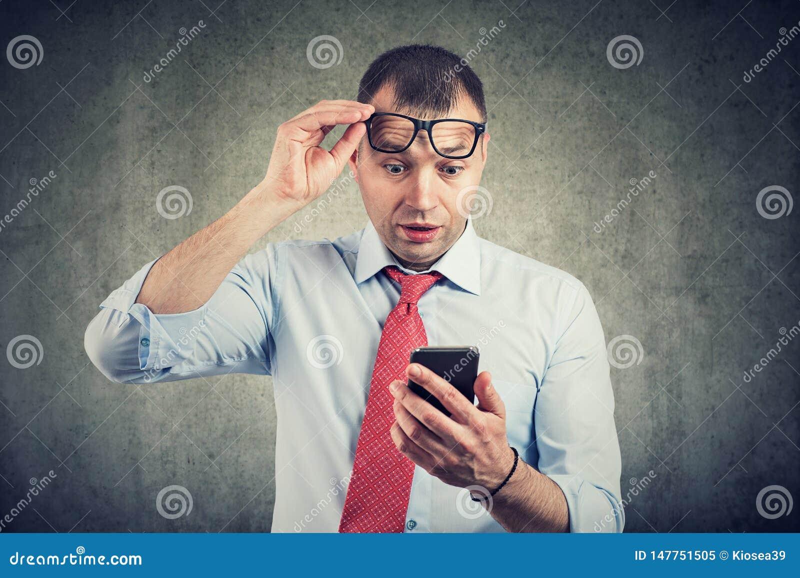 Uomo d affari in occhiali che guarda smartphone nel messaggio della lettura di scossa