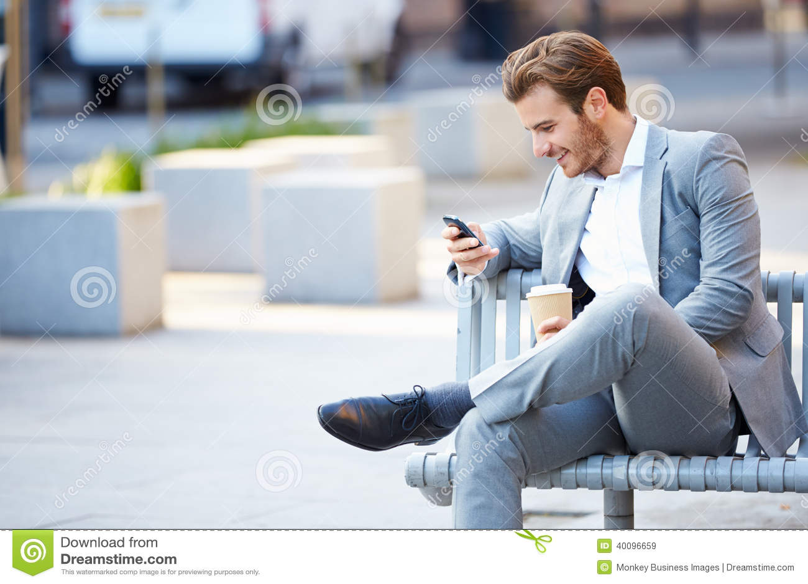 Uomo d affari On Park Bench con caffè facendo uso del telefono cellulare