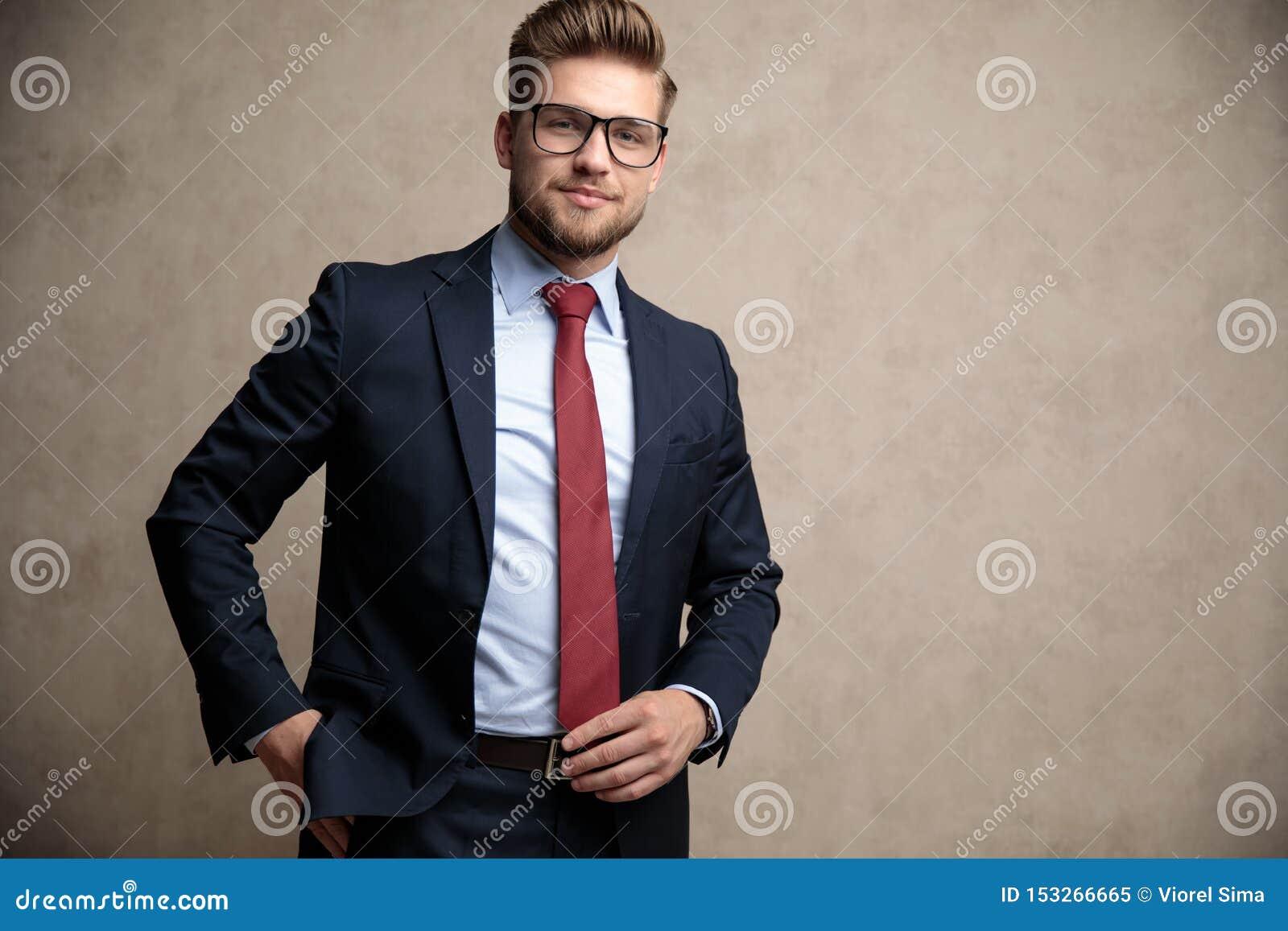 Uomo d affari positivo che regola il suoi legame e stare